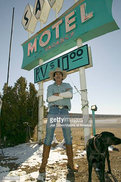Cowboy with dog stand in front of Sands Motel sign with RV Parking for $10, located at the intersection of Route 54 & 380 in Carrizozo, New Mexico