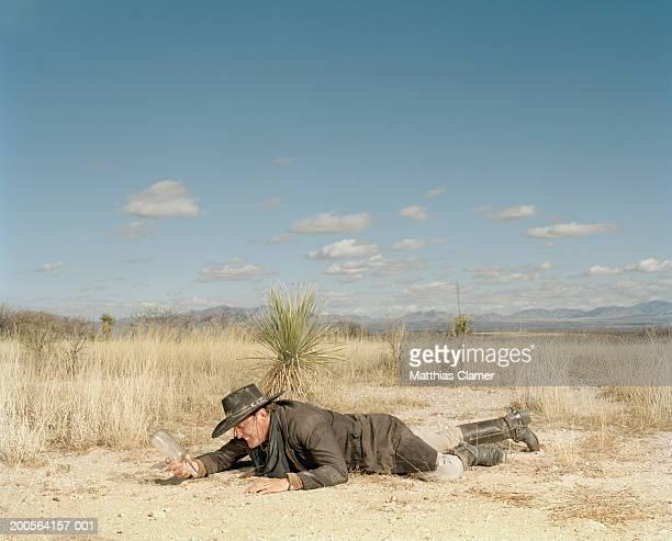 Cowboy with empty bottle in desert