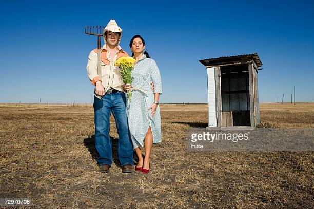 Cowboy with wife, holding a pitchfork and flowers