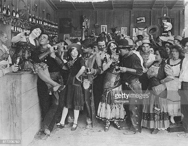 Cowboys and bar girls whoop it up in a still from an old silent Western