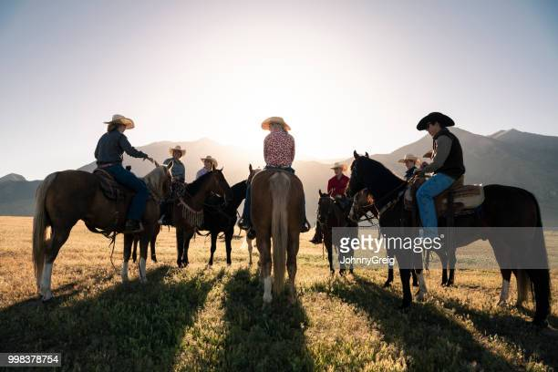 cowboys and cowgirls on horses at sunrise - recreational horseback riding stock pictures, royalty-free photos & images