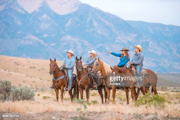 Cowboys and cowgirls riding a horse in nature