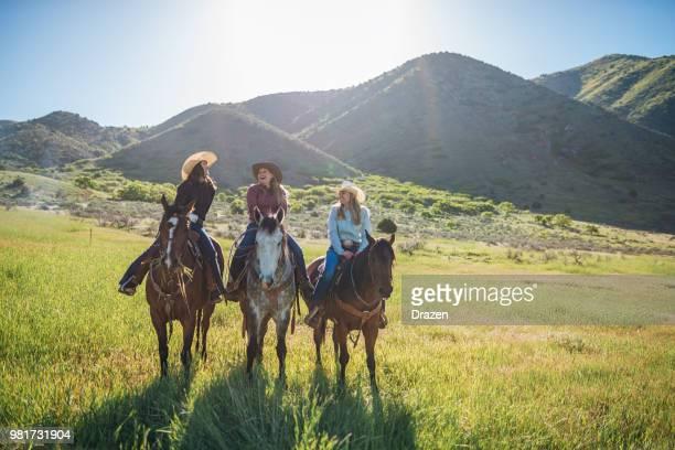 cowboys et cowgirls, monter à cheval dans la nature - cowgirl photos et images de collection