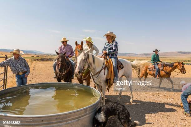 cowboys and cowgirls watering their horses - water tower storage tank stock pictures, royalty-free photos & images