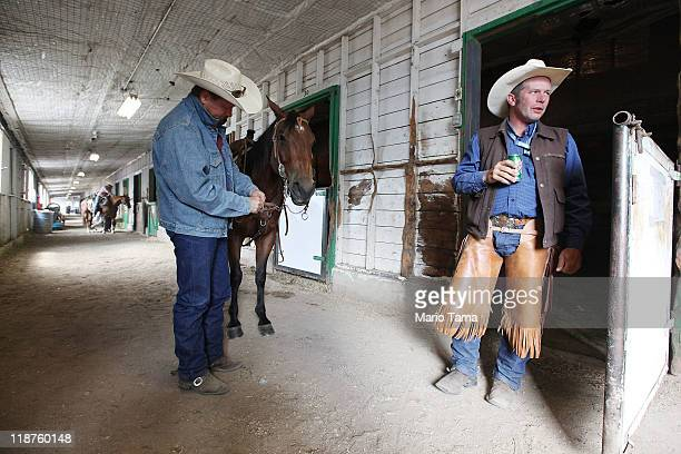 Cowboys Chris Redden and Runt Rageth prepare to compete in a barn at the Calgary Stampede on July 10 2011 in Calgary Canada The tenday event...