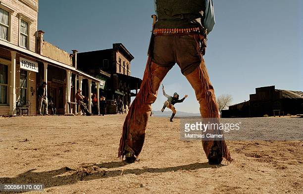 Cowboys having gun duel in old west town