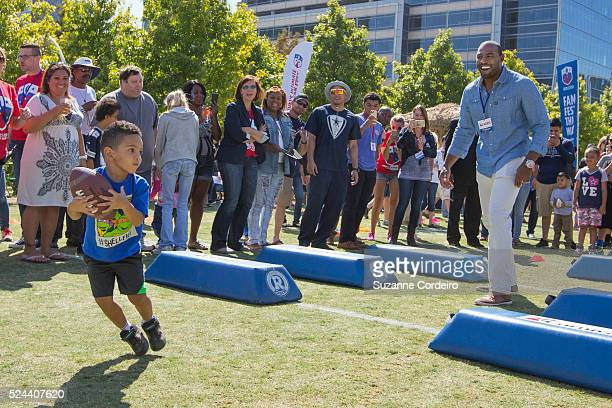 Cowboys legend Darren Woodson throws pass to a young fan during a football drill at Carnival's Ultimate Cowboys Fan Fest on October 18 2015 at Klyde...
