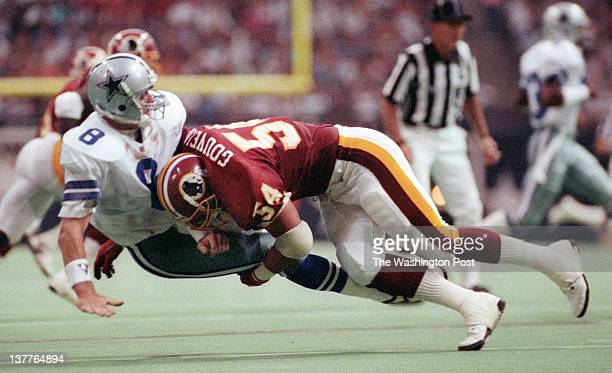 Cowboys quarterback Troy Aikman is slammed into the turf by Redskins linebacker Kurt Gouveia during the the Washington Redskins defeat of the Dallas...