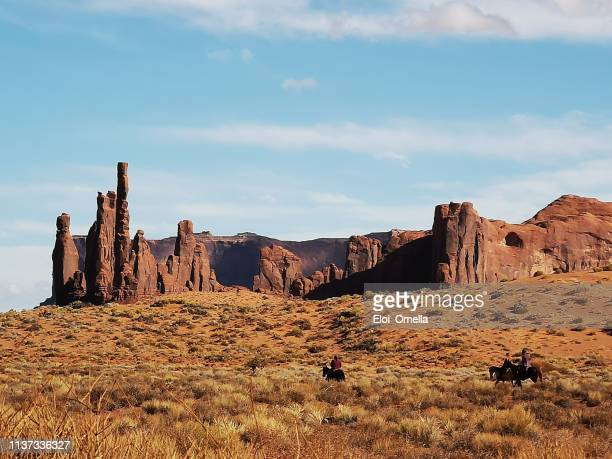 cowboys riding horse in the landscape of monument valley - monument valley tribal park stock photos and pictures