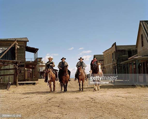 Cowboys riding horses through town