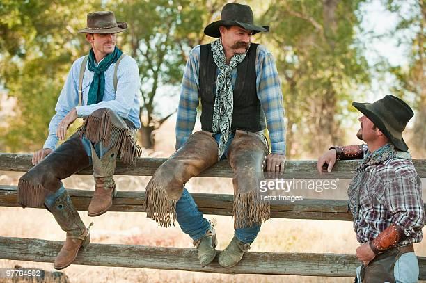 cowboys sitting on fence - pantalón de cuero fotografías e imágenes de stock