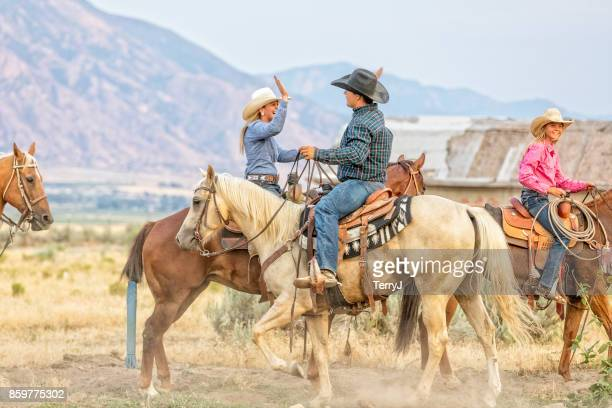 cowgirl and cowboy congratulate each other while on horseback - texas stock pictures, royalty-free photos & images
