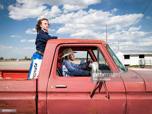 Cowgirl and cowboy in pickup truck