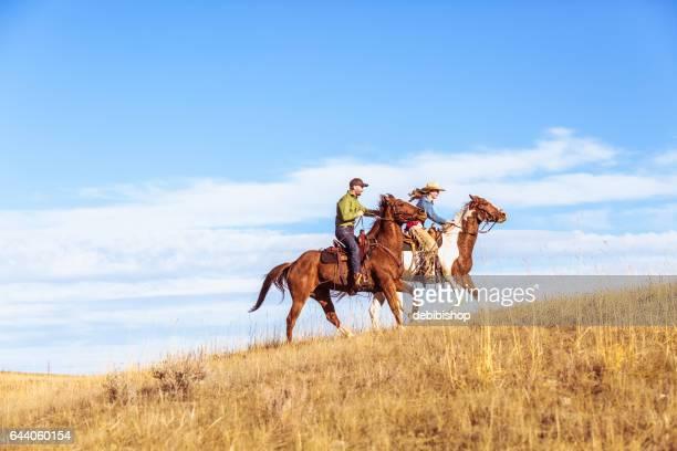 Cowgirl And Cowboy Racing Uphill On Horseback