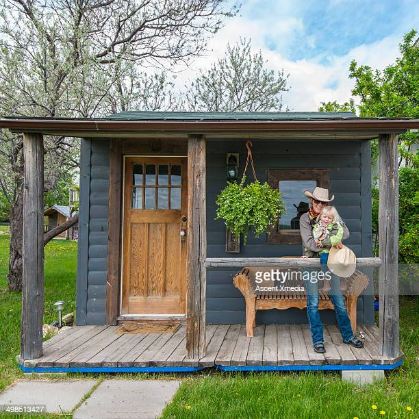 Cowgirl and daughter relax on veranda, range home