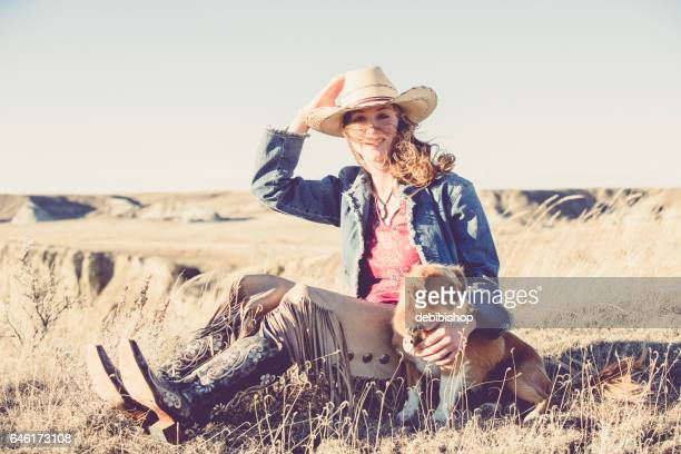 cowgirl and her little dog - istock photo stock pictures, royalty-free photos & images