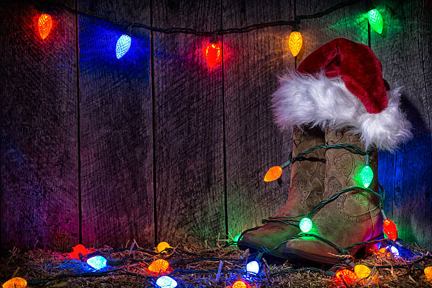 Cowgirl Boots At Christmas Time With Lights And Santa Hat