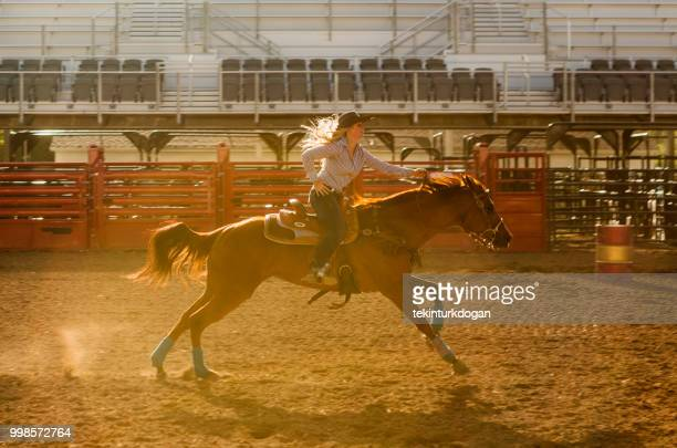 cowgirl cowboy riding horse at rodeo