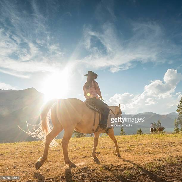 Cowgirl follows companions across mountain meadow