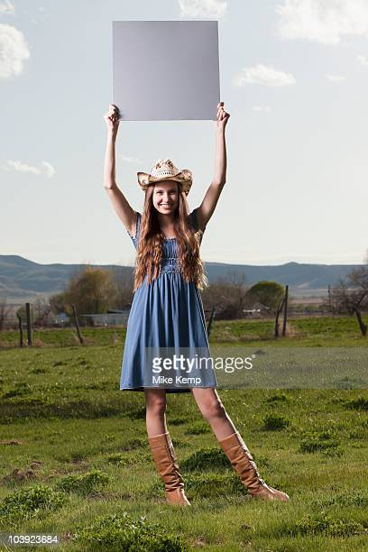 cowgirl holding up blank poster while standing in field - blank sign stock photos and pictures