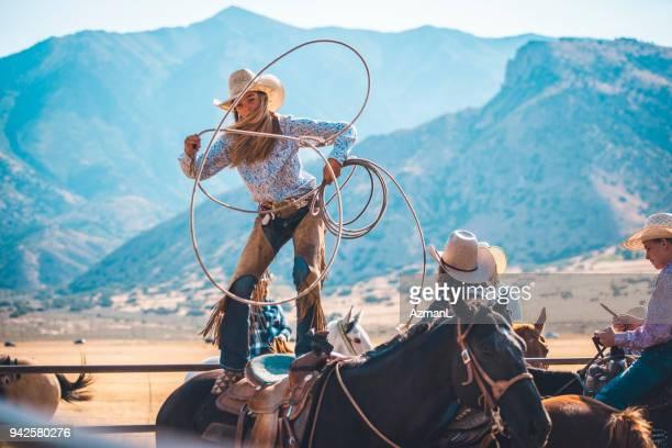 cowgirl in rodeo arena lassoing - cowboy stockfoto's en -beelden