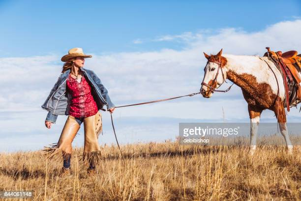 Cowgirl Leading Her Horse By The Reins