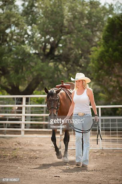 Cowgirl leading horse out of a corral