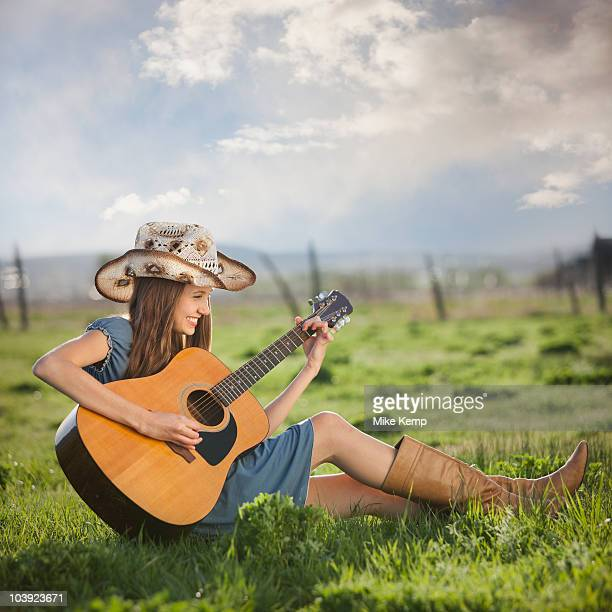 Cowgirl playing guitar in field
