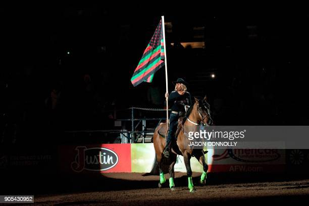 A cowgirl presents the Black American National Flag at the start of the MLK Jr African American Heritage Rodeo at the National Western Stock Show in...
