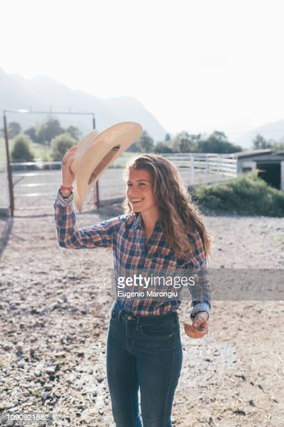 cowgirl putting on stetson in rural equestrian arena - cowgirl hairstyles stock photos and pictures