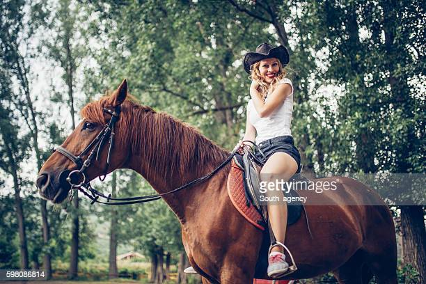 Cowgirl ridding a brown horse
