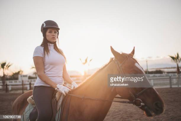cowgirl riding a black stallion horse - female animal stock pictures, royalty-free photos & images