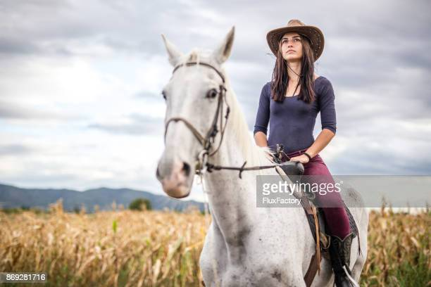 cowgirl riding a horse - rein stock pictures, royalty-free photos & images
