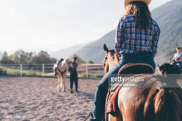 cowgirl riding horse in rural equestrian arena, primaluna, trentino-alto adige, italy - cowgirl hairstyles stock photos and pictures