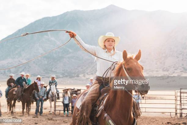 Cowgirl riding on horse throwing lasso in rodeo training