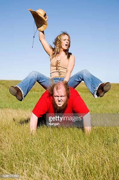 Cowgirl Reiten auf Mannes zurück in das Feld
