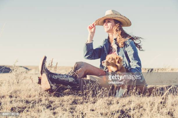 cowgirl sitting outdoors with her dog - istock photo stock pictures, royalty-free photos & images