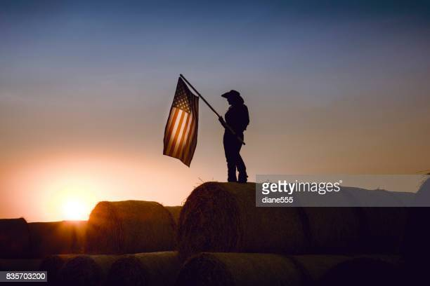 Cowgirl Standing On Top  Bales Of Hay Holding An American Flag