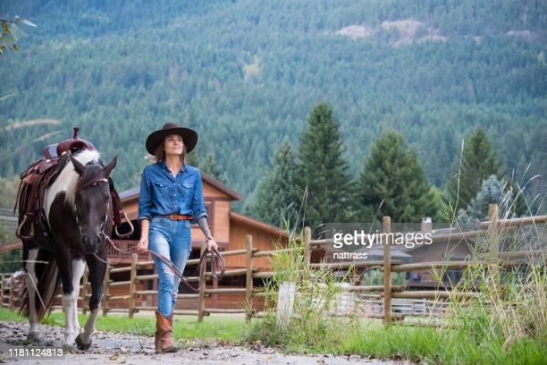 cowgirl che cammina con il suo cavallo - ranch foto e immagini stock