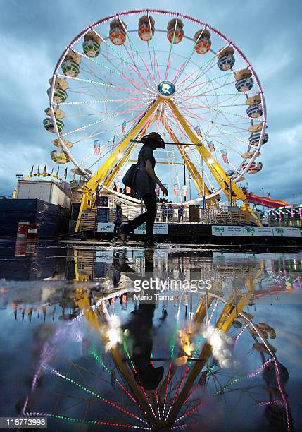 A cowgirl walks past a ferris wheel at the Calgary Stampede on July 10 2011 in Calgary Canada The tenday event featuring over one million visitors is...