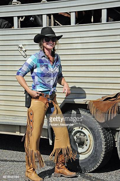 A cowgirl wearing chaps and boots loads horses into a trailer after helping guide a group of park visitors on a horseback ride in Grand Teton...