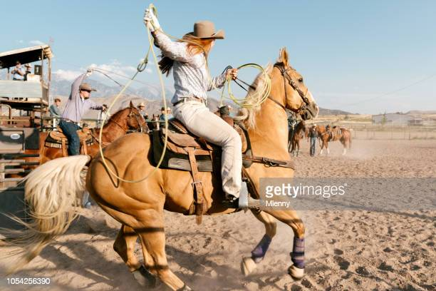 Cowgirl with lasso starting into rodeo arena