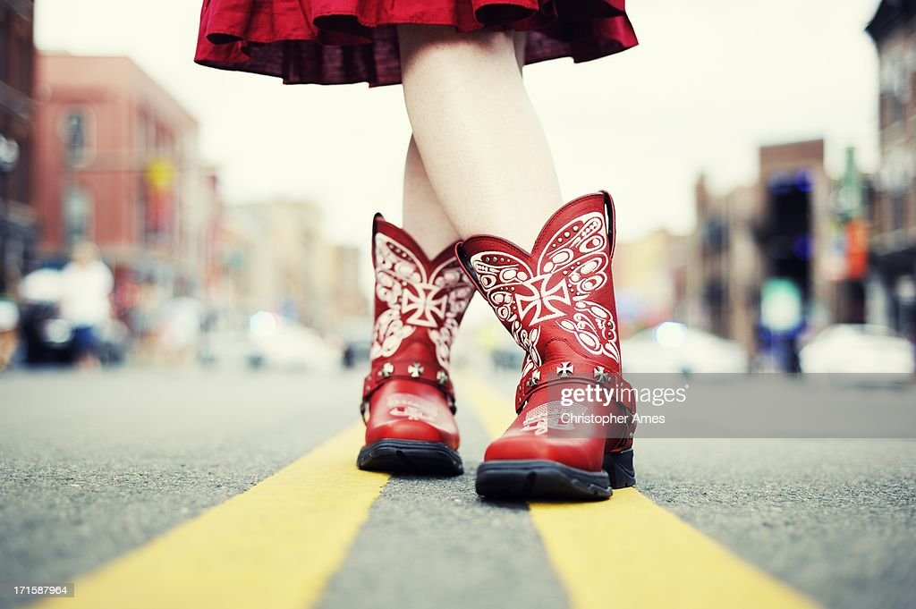 Cowgirl with Red Boots in the Road : Stock Photo