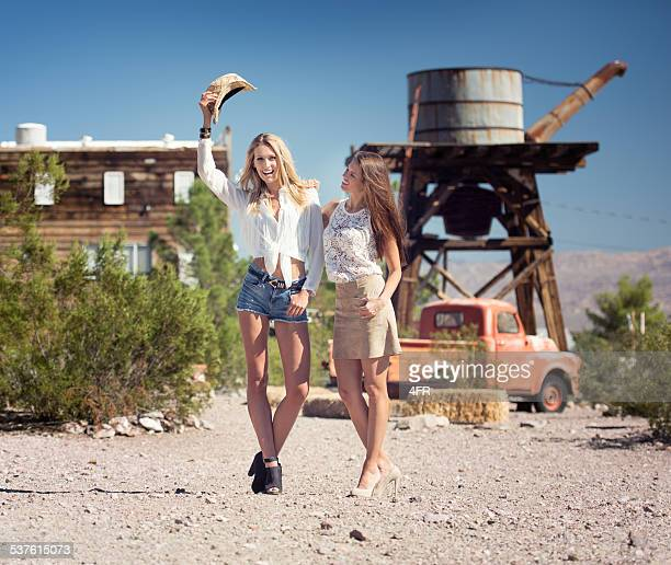 cowgirls at an old western town - hot legs stock photos and pictures