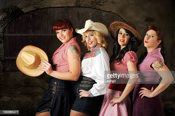 Cowgirls chorus line against barn door