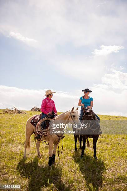 Cowgirls discuss range issues while on horseback