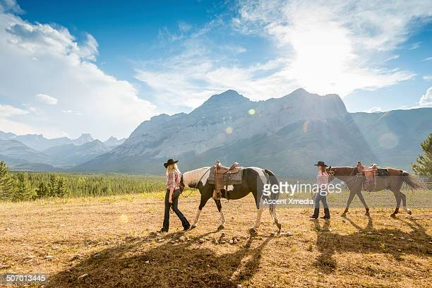 Cowgirls lead horses across mountain rangeland