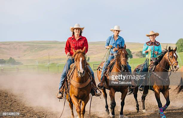 cowgirls riding horses on ranch - cowgirl photos et images de collection