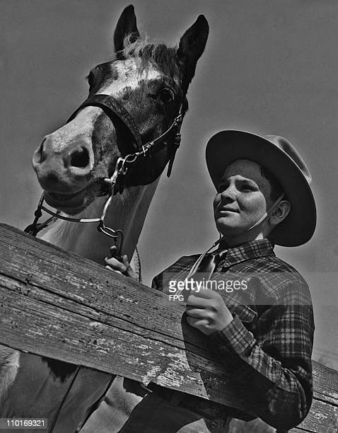 Cowhand Morris Smith on the corral guard rail with his pony Flash Flash and the allwestern outfit were Christmas presents from his father Thomas J...