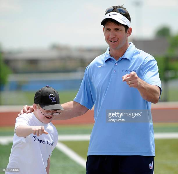 RANCH COWill Harmon 10yearsold left with Down Syndrome and former Denver Bronco Ed McCaffrey during a pep talk after football drills at Valor...